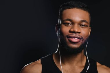 handsome young african american man in earphones smiling at camera isolated on black