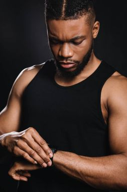 serious muscular african american man using smartwatch on black