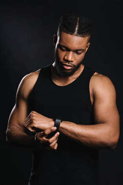 handsome serious african american sportsman using smartwatch isolated on black