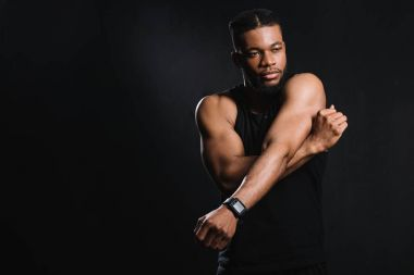 muscular african american man stretching hands isolated on black