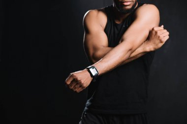 cropped shot of muscular african american man stretching hands isolated on black