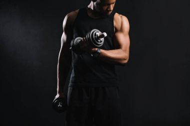 cropped shot of muscular african american man exercising with dumbbells and looking at biceps on black