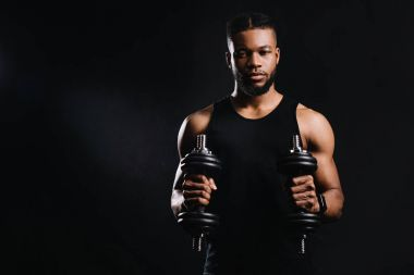 muscular young african american sportsman holding dumbbells and looking at camera isolated on black