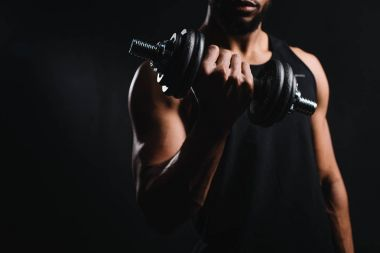 cropped shot of muscular african american man exercising with dumbbell isolated on black
