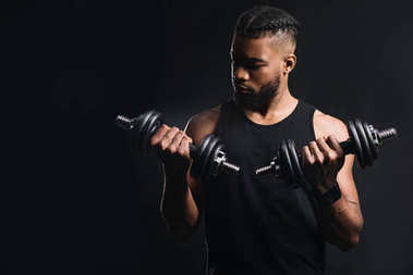 handsome muscular african american man exercising with dumbbells isolated on black