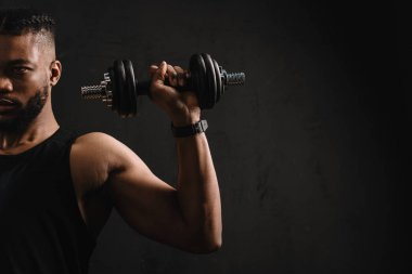 cropped shot of muscular african american man training with dumbbell isolated on black
