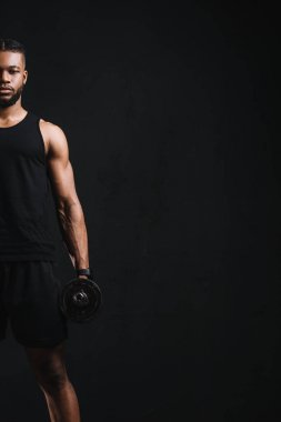 cropped shot of young african american sportsman holding dumbbell isolated on black