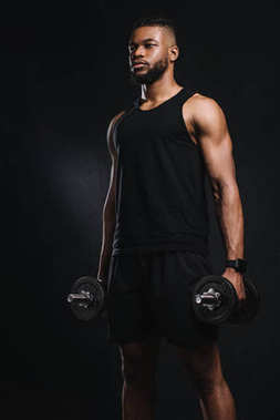 muscular young african american man holding dumbbells and looking away isolated on black
