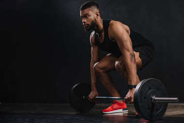 muscular young african american sportsman lifting barbell and looking away on black