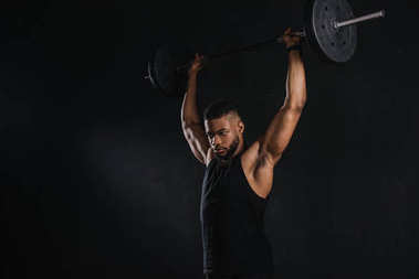 muscular young african american sportsman lifting barbell and looking away isolated on black
