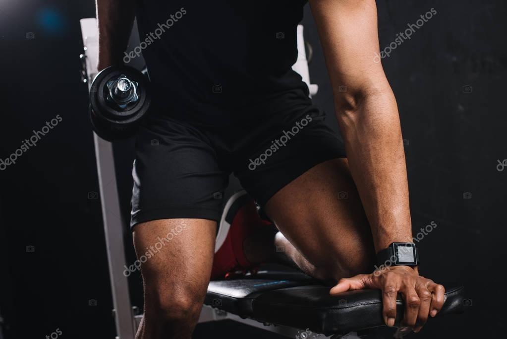 cropped shot of muscular african american sportsman training with dumbbell in gym