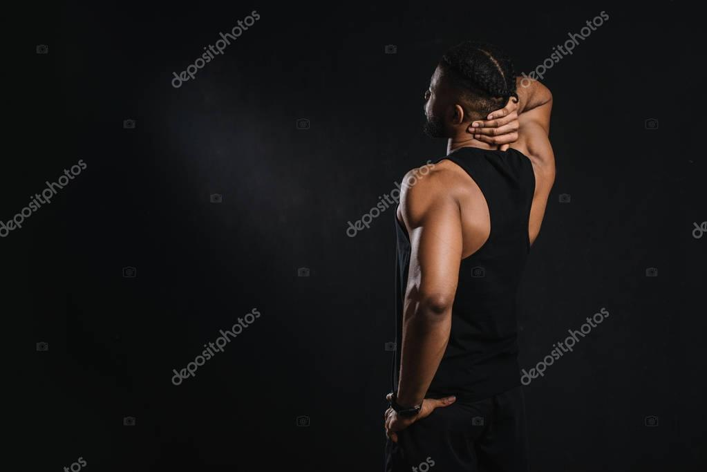 back view of young african american sportsman looking away isolated on black