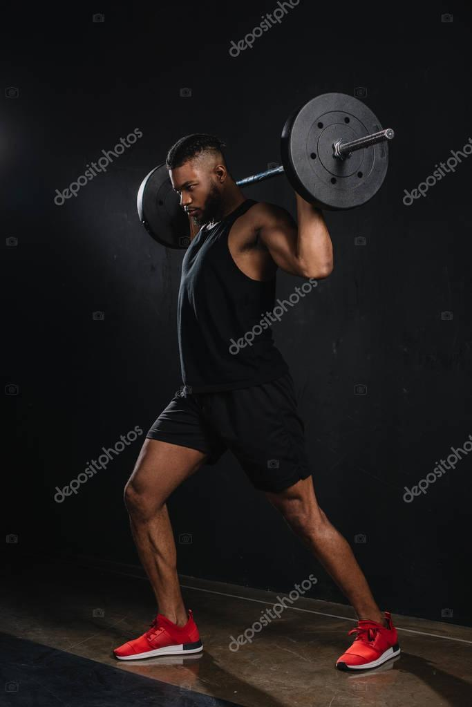muscular young african american sportsman lifting barbell on black