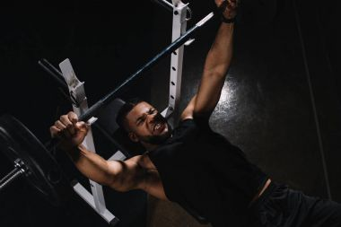 high angle view of young african american sportsman lifting barbell