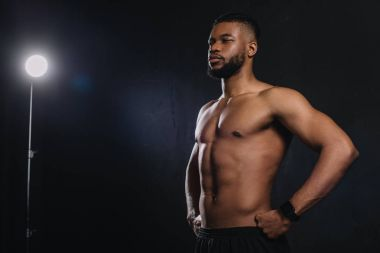 muscular young african american sportsman standing with hands on waist and looking away on black