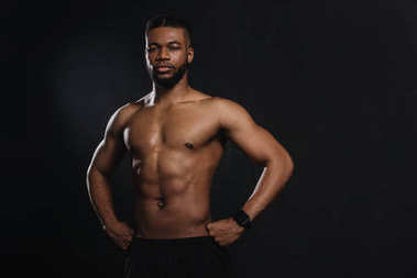 muscular young african american sportsman standing with hands on waist and looking at camera isolated on black