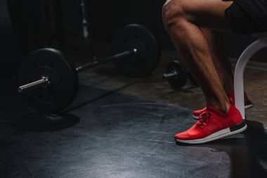 cropped shot of african american sportsman in sneakers training in gym