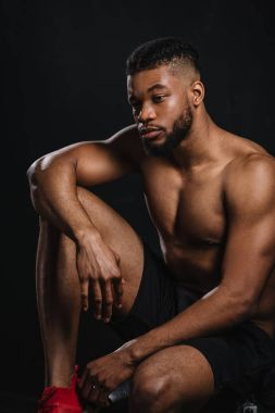 pensive shirtless young african american sportsman sitting and looking away on black