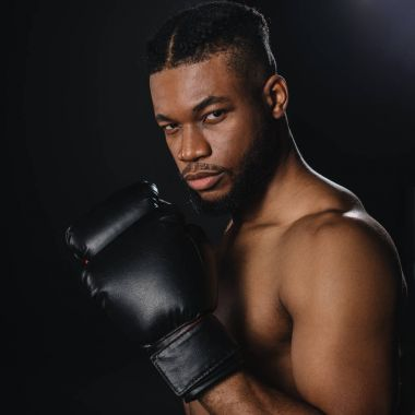 serious shirtless african american boxer in boxing gloves looking at camera isolated on black
