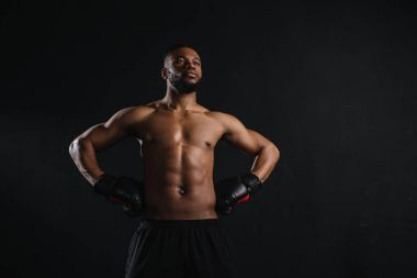 muscular shirtless african american man in boxing gloves standing with hands on waist and looking away isolated on black