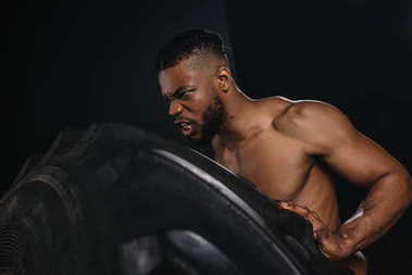 side view of muscular young african american sportsman lifting tire on black