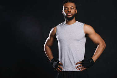 handsome young african american sportsman standing with hands on waist and looking at camera isolated on black