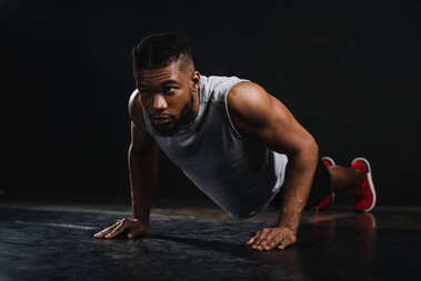 Young muscular african american man in sportswear doing push-ups and looking away on black stock vector