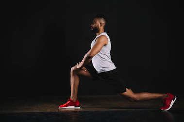 side view of athletic young african american man in sportswear exercising and looking away on black