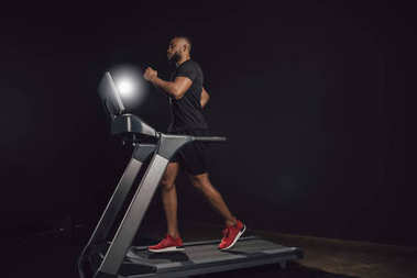 side view of athletic young african american man running on treadmill on black