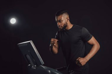 athletic young african american man running on treadmill on black