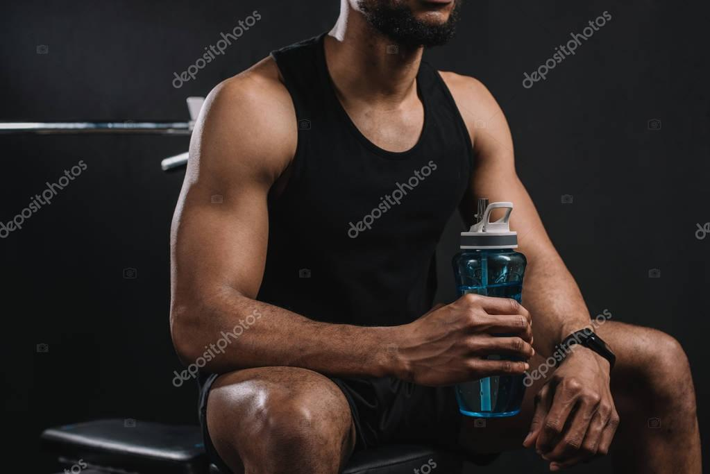 cropped shot of muscular african american sportsman sitting and holding bottle of water