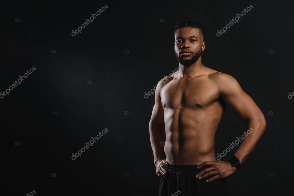 muscular shirtless african american man standing with hands on waist and looking at camera isolated on black