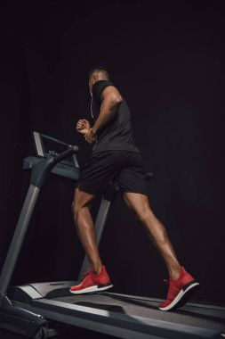 low angle view of young african american sportsman running on treadmill isolated on black