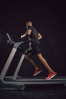 low angle view of young african american sportsman running on treadmill on black