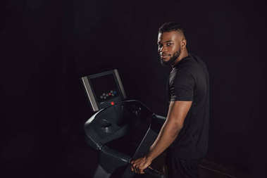 young african american sportsman exercising on treadmill and looking at camera isolated on black