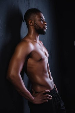 side view of muscular shirtless young african american man standing with hands on waist and looking away on black
