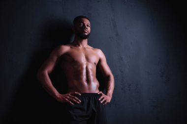 low angle view of muscular shirtless young man standing with hands on waist and looking away on black
