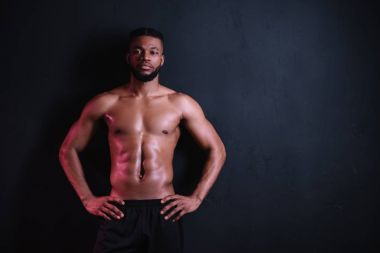 muscular bare-chested african american man standing with hands on waist and looking at camera isolated on black