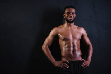 shirtless muscular young african american man standing with hands on waist and smiling at camera on black