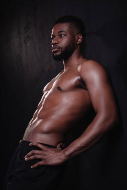 muscular shirtless young african american man standing with hands on waist and looking away on black