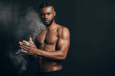 young bare-chested african american sportsman applying talcum powder and looking at camera on black