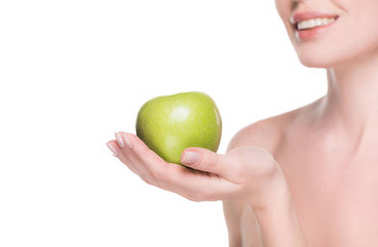 Cropped view of woman with clean skin holding apple isolated on white