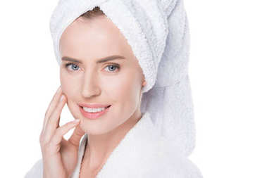 Woman with clean skin in bathrobe and towel on hair touching own face isolated on white