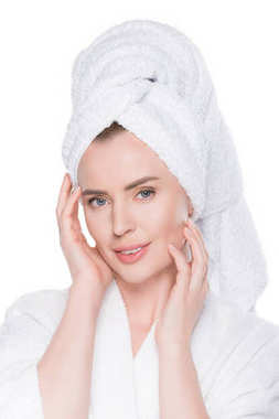 Portrait of woman with clean skin in bathrobe and towel on hair touching own face isolated on white