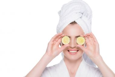 Woman with clean skin closing eyes by slices of lime isolated on white