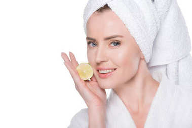 Portrait of woman with fresh clean skin holding slice of lime isolated on white