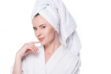 Female with clean skin wearing bathrobe and towel on hair holding finger on chin isolated on white