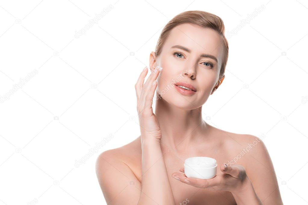 Woman with clean skin applying cream on face isolated on white