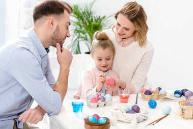Parents and daughter painting Easter eggs in different colors
