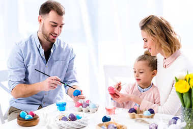 Family coloring Easter eggs with painting brushes